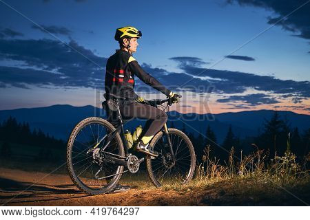 Side View Of Young Man On Bicycle Under Blue Night Sky With Clouds. Male Bicyclist In Safety Helmet