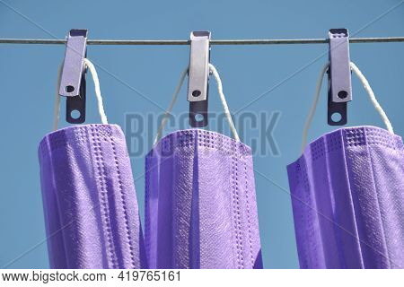 Front View Of Blue Color Surgical Face Mask Hanging On Clothesline Wire With Clothespin, Concept Of