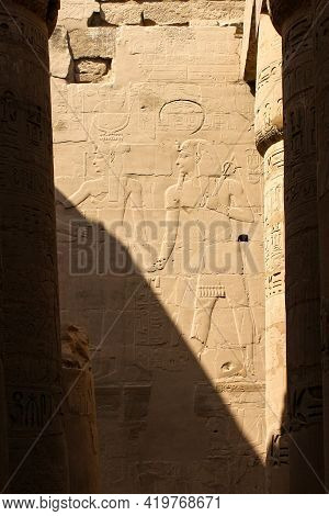 Karnak Temple Complex In Luxor, Egypt. Ancient Bas Relief With Hieroglyphs, Pharaoh And Goddes.