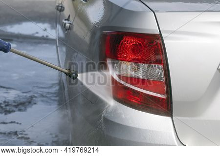 Cleaning The Rear Red Lights Of A Gray Car In Close-up With A High-pressure Washer. A Stream Of Wate