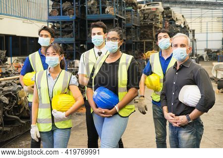 Men And Woman Work Together, Show Teamwork By Holding Helmets And Wear Facemask. Caucasian Engineer