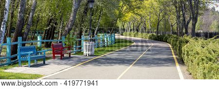 Walkway Through The Park, Benches For Relaxation. Beautiful Spring Nature. Panorama Of The Spring Pa