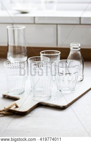 Transparent glassware on a wooden cutting board