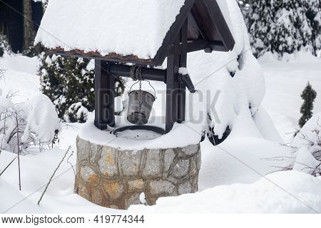 Snow Covered Water Well With Metal Bucket