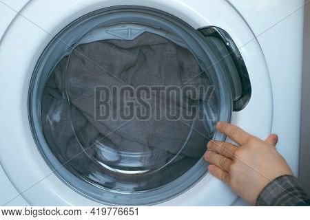 Mans Hands Loading The Washing Machine With Bedspread, Laundry At Home. Man Is Doing His Laundry And