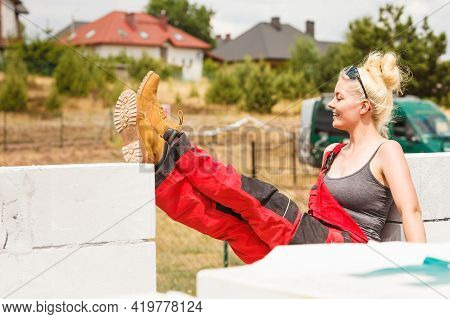 Blonde Woman Wearing Dungarees Relaxing After Hard Work On Construction Site. Female Taking Break Dr