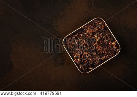 Close Up Tin Full Of Ready Rubbed Long Coarse Cut Pipe Tobacco Blend Over Grunge Brown Background, E