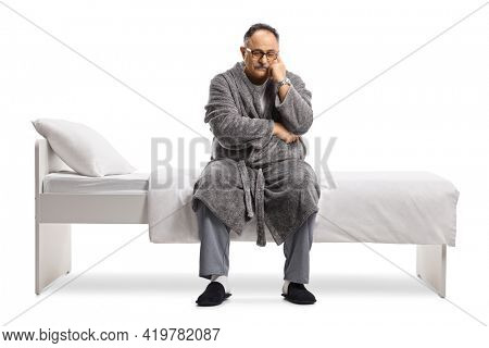 Pensive and sad mature man in pajamas and a robe sitting on a bed isolated on white background