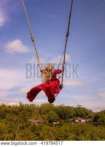 Bali Swing Trend. Caucasian Woman In Long Red Dress Swinging In The Jungle Rainforest. Vacation In A