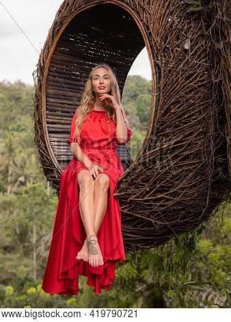 Bali Trend. Straw Nest In Tropical Forest. Caucasian Woman In Long Red Dress Taking Photo In A Straw