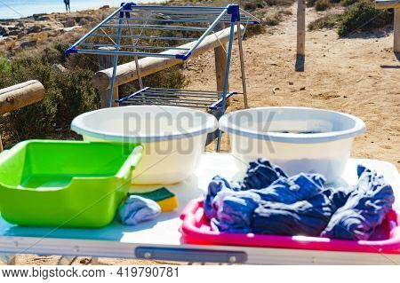 Washing Clothing Laundry Outdoor At Campsite. Bowl With Soap Water And Laundry Dryer. Camping