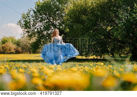 A Young Cheerful Girl Runs In A Blue Long Dress, Across A Field With Yellow Meadow Flowers. A Summer