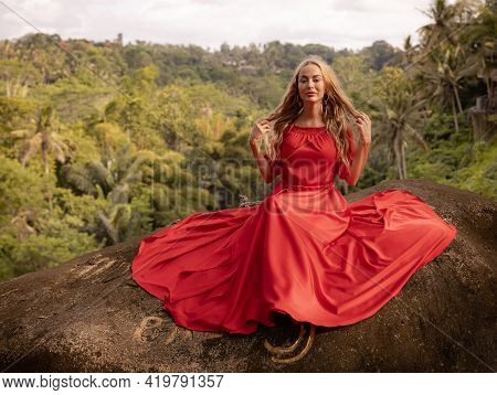 Bali Trend Photo. Caucasian Woman In Long Red Dress Sitting On Big Stone In Tropical Rainforest. Vac
