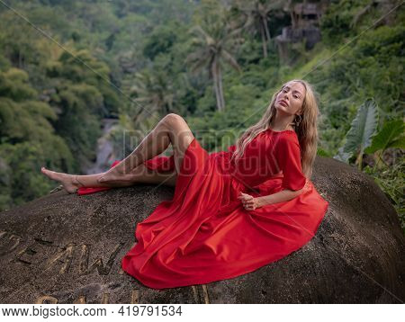 Bali Trend Photo. Caucasian Woman In Long Red Dress Lying On Big Stone In Tropical Rainforest. Vacat