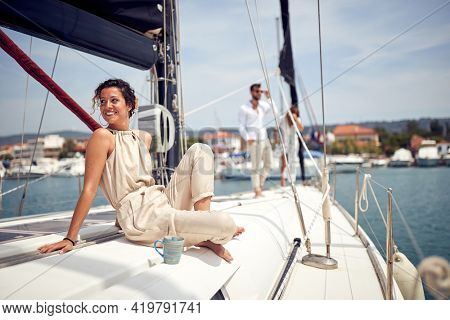 A young beautiful girl is enjoying the sun while spending a wonderful time on a yacht with friends on a beautiful summer day on the seaside. Summer, sea, vacation, friendship