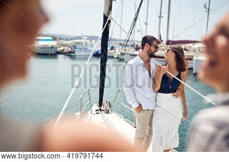 A young couple in a hug is enjoying a wonderful time with friends on a yacht on a beautiful summer day on the seaside. Summer, sea, vacation, relationship