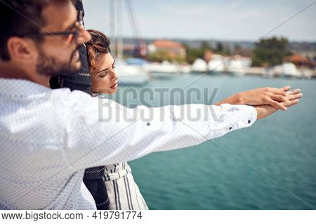 A young couple is enjoying romantic moments on the bow of the yacht together while riding on a beautiful summer day on the seaside. Summer, sea, vacation, relationship