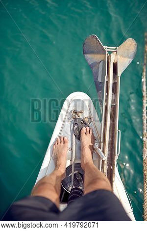 A barefoot man is standing on the bow of a yacht on a beautiful summer day at sea. Summer, sea, vacation