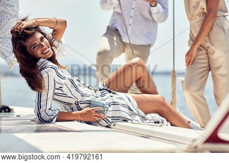 A young handsome female model is relaxing and posing for a photo while spending a wonderful time with her friends at a photo shooting on a yacht on a beautiful sunny day on the seaside. Summer, sea, v