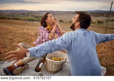 A young couple is enjoying and shouting on the picnic on a large meadow on a beautiful day. Relationship, together, love, picnic