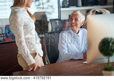 A female boss talking to her young female colleague in a pleasant atmosphere at the workplace. Business, office, job