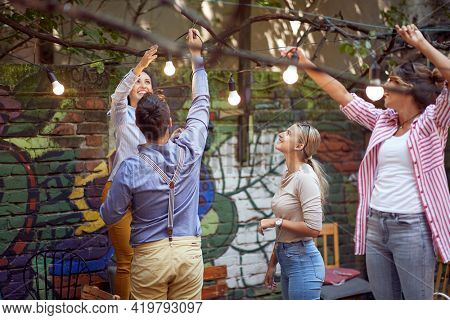 A group of cheerful friends preparing a bar's garden for a party on a beautiful day. Leisure, bar, friendship, outdoor