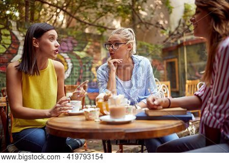 A group of female students is gossiping while having a drink in a bar's graden on a beautiful day. Leisure, bar, friendship, outdoor