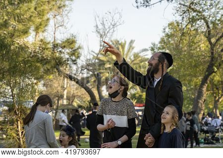 Tel Aviv, Israel - March 31st, 2021: A Father And His Children Looking At People Using A Rope Advent