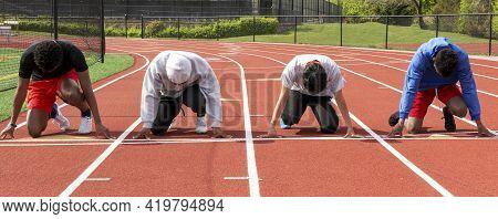 Front View Of Four High School Boys Sprinters Ready On Their Mark To Run A Sprint Race Against Each