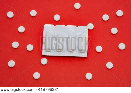 Plastic Packaging With Vaginal Or Rectal Suppositories Is On Redbackground Surrounded By Round Table