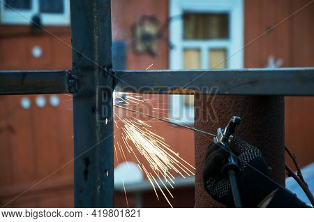 Welding Work On The Street. The Welder Will Produce Metal Parts On The Site. Welding Of The Metal Fr