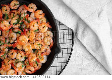 Prawns Fried With Garlic In A Cast Iron Skillet On A White Table With A White Linen Napkin. Top View
