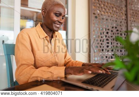African Woman Working On Laptop In Bar Restaurant - Afro Female Typing On Computer - Digital Nomad A