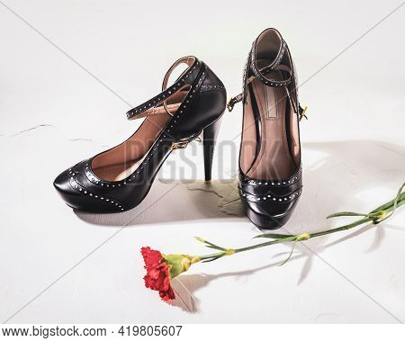 Composition With A Pair Of Black Women's High-heeled Shoes With A Scarlet Carnation Flower On A Whit