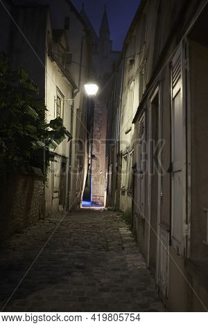 Narrow Alley With Cobblestones In French Town At Night Illuminated By One Lantern