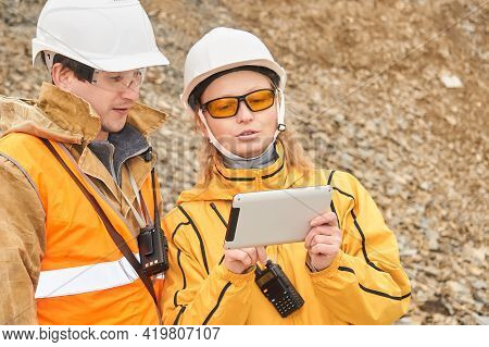 Mining Engineers Discussing Working Documentation Outdoor At The Mining Site