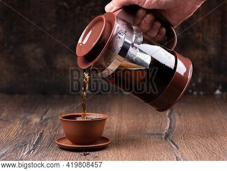 Pouring Freshly Brewed Tea Into A Clay Cup. Brewing Tea.