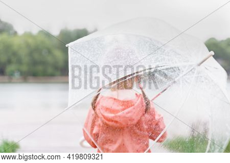 Child With Transparent Umbrella Looks At The River On A Rainy Day, Back View. Rainy Season