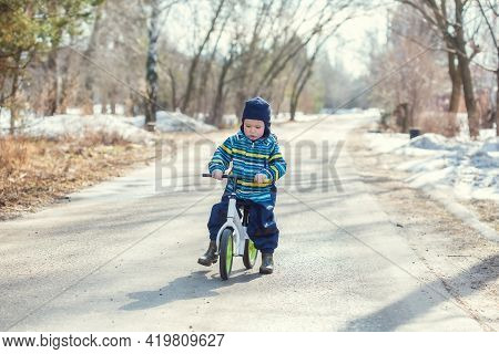 A Little Caucasian Boy 2 Years Old Learns To Ride A Balance Bike On The Road In The Village In The S