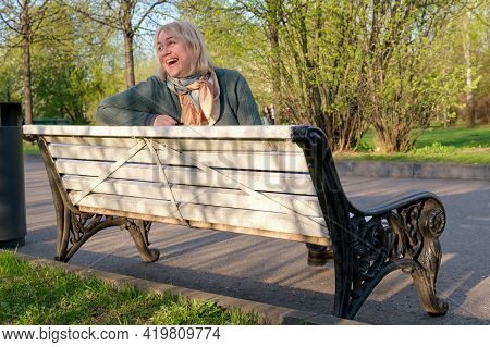 Middle-aged Woman With Blond Hair Sits On A Park Bench And Laughs. Laughing Woman. Walk In The Sprin
