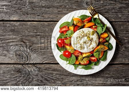 Burrata Caprese Salad With Spinach And Basil Pesto Sauce On A White Plate On A Wooden Table, Horizon