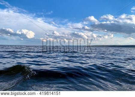 Sea Ripples. Bright Background. Dark Blue Water. Shallow Waves And Sun Glare On The Water. Abstract.