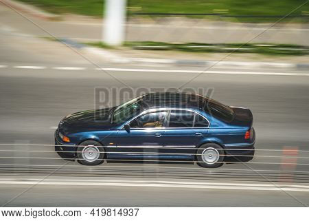 Old Blue Bmw E39 On The City Road. Fast Moving Car On The Street. Vehicle Driving Along The Street I