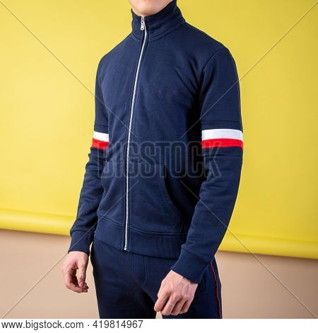 Guy In A Dark Blue Tracksuit On A Yellow Background