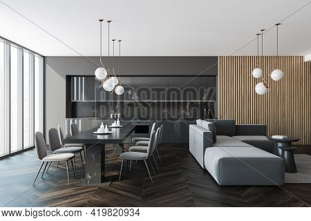 Interior Of Modern Kitchen With Wooden Floor, Furniture, Table And Chairs, Big Couch In The Middle O