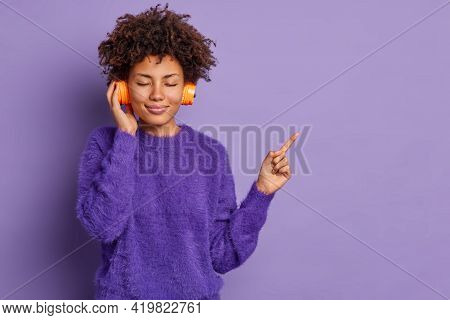 Pleased Young Curly African American Woman Keeps Eyes Closed Has Curly Hair Enjoys Favorite Melody D