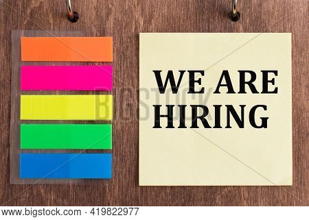 We're Hiring, Text On Sticker On Wooden Background, Business Concept