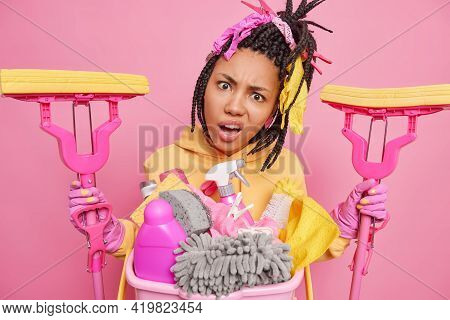 Displeased Indignant Young Afro American Woman With Combed Braids Holds Two Mops Tilts Head Wears Ru