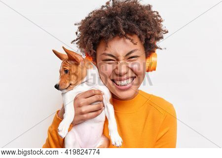 People Animals Friendship Concept. Overjoyed Curly Haired Woman Smiles Tenderly Holds Small Pedigree
