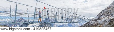 Panorama View Of A Girl With Swiss Flag On Titlis Cliff Walk Suspension Bridge. Top Of Titlis Mounta